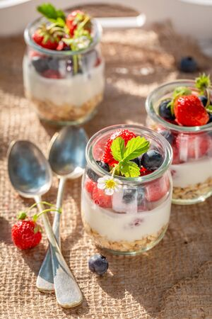 Oat flakes in jar with yoghurt and berries