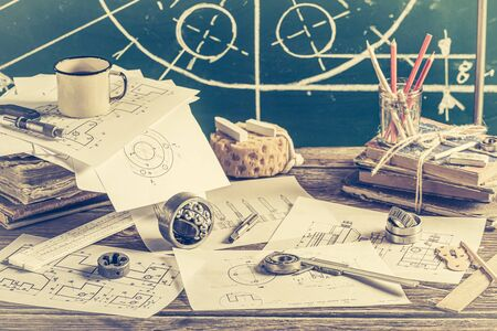 Vintage designer desk of mechanical parts on green chalkboard background