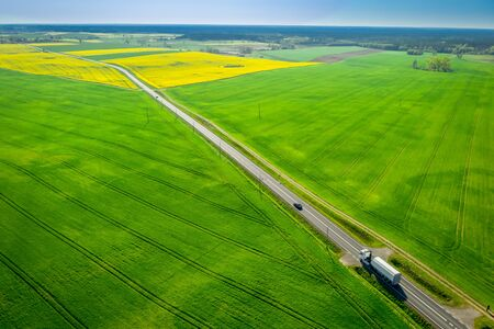 Moving cars on a road between green fields in Poland
