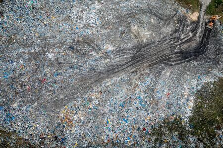 Bulldozer on open solid waste dump, Poland from above