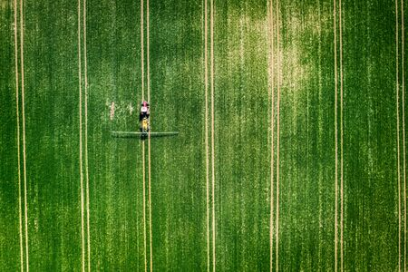Tractor spraying the chemicals on the field, Poland from above
