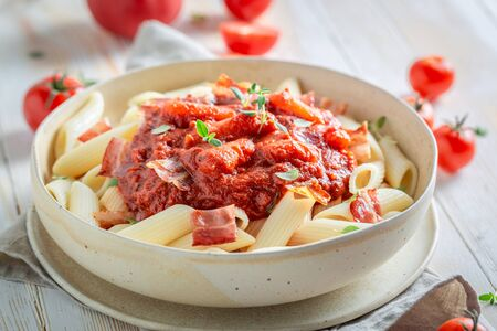 Tasty penne bolognese made of fresh tomatoes and hebrs Фото со стока - 126979512