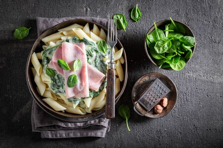 Delicious penne with ham, spinach and bechamel sauce