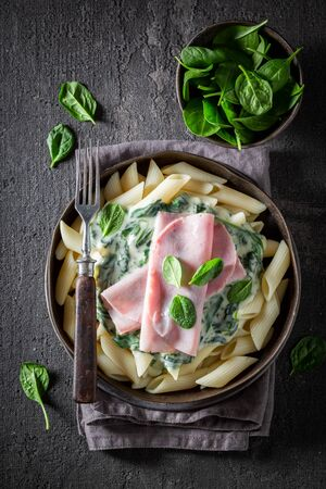 Tasty penne with spinach, bechamel sauce and ham Фото со стока