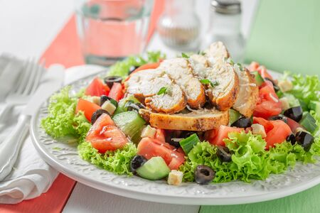 Fresh Caesar salad with cucumber, tomatoes and chicken