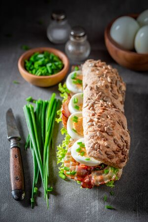 Delicious sandwich with bacon, chive and eggs Stockfoto