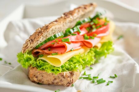 Tasty sandwich with cheese, ham and chive for breakfast Foto de archivo - 126979586
