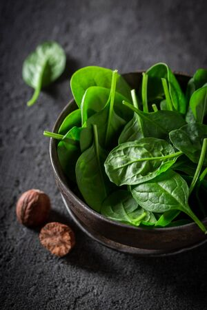 Raw green spinach in small rustic brown bowl