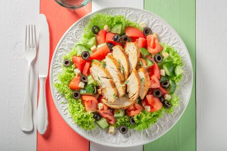 Healthy Caesar salad with cucumber, tomatoes and chicken Фото со стока