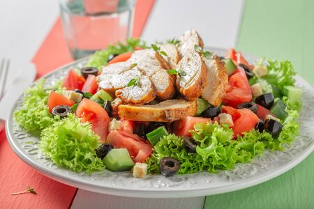 Fresh Caesar salad with chicken, tomatoes and lettuce