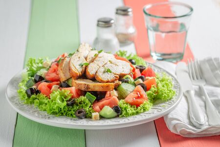 Delicious Caesar salad with tomatoes and lettuce and olives Фото со стока