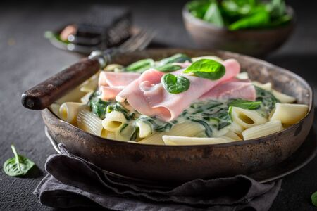 Delicious penne with spinach, bechamel sauce and ham