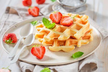 Gaufrettes savoureuses avec des fraises sucrées et du sucre en poudre