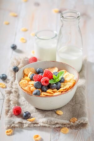 Delicious cornflakes with berries and milk for breakfast
