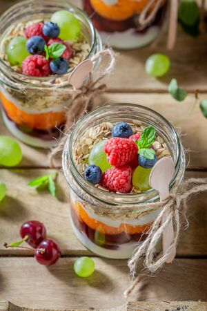 Homemade oat flakes in jar with yoghurt and fresh berries