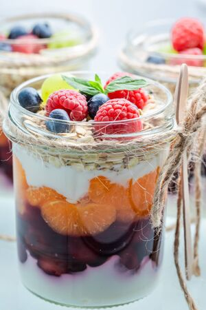 Closeup of granola in jar with berry fruits and yoghurt