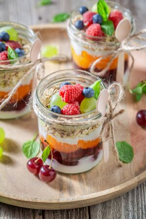 Healthy granola with fresh berries and yoghurt in jar