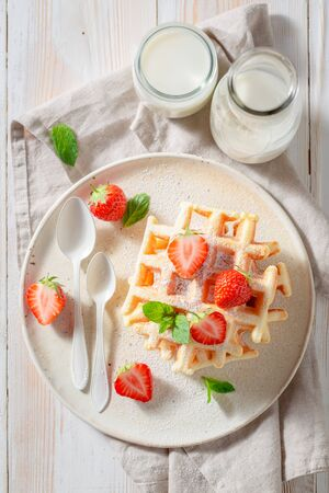 Tasty wafers with powdered sugar and sweet fruits