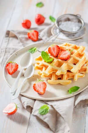 Delicious wafers with sweet strawberries and powdered sugar