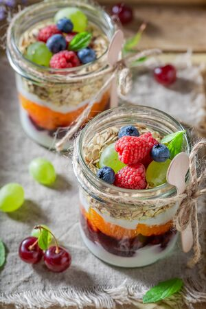 Tasty granola with fresh berries and yoghurt in jar