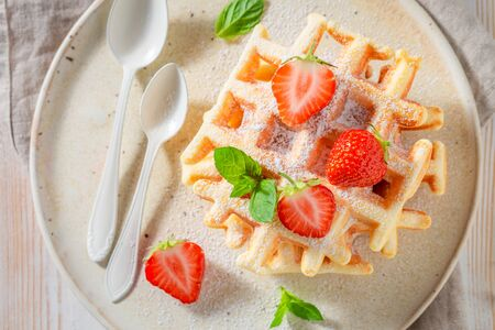 Fresh wafers with sweet strawberries and powdered sugar Stock Photo - 127587718