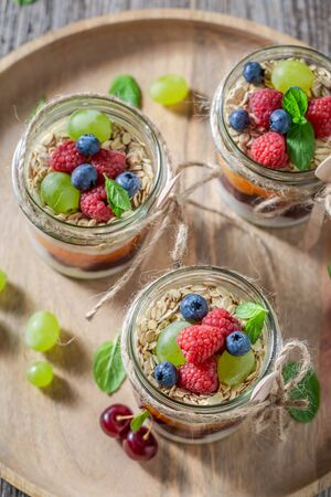 Healthy granola in jar with yoghurt and fresh berries Stock Photo