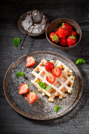 Fresh wafers with powdered sugar and sweet fruits Stock Photo - 127587687