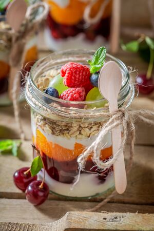 Homemade oat flakes with fresh berries and yoghurt in jar