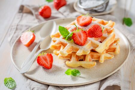 Homemade wafers with powdered sugar and sweet fruits