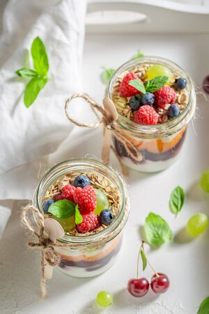 Tasty granola in jar with yoghurt and fresh berries