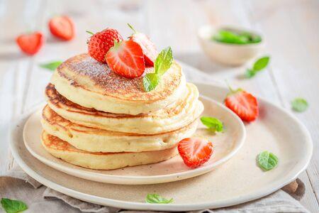 Deliciosos panqueques americanos con azúcar en polvo y fresas dulces