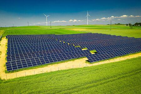 Niesamowity widok na panele słoneczne i turbiny wiatrowe latem