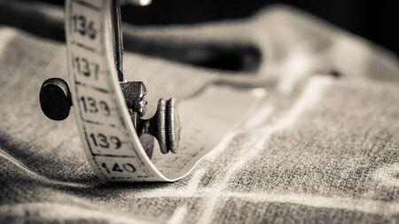 Close-up van vintage kleermakersmachine met schaar, doek en draden
