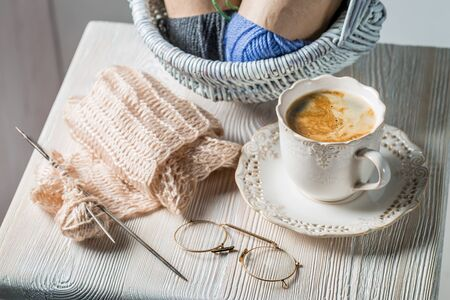 Handmade knitted scarf made of colored woolon white table Stock Photo