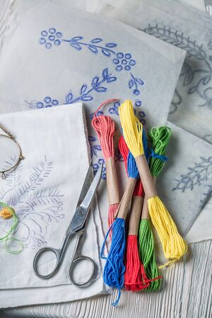Top view of colored threads and embroidered napkins