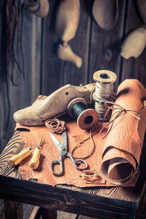 Closeup of cobbler workplace with tools, shoes and leather Stock Photo