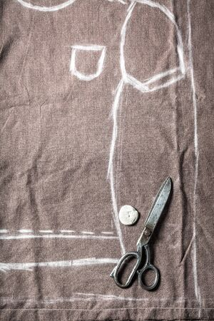 Closeup of tailor pattern, scissors and clothes in tailoring workshop