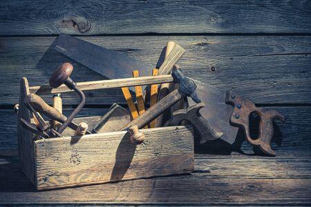 Vintage timmermansdoos met gereedschap op rustieke houten tafel Stockfoto