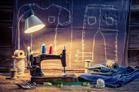 Cloth, sewing machine and scissors in tailoring workshop