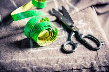 Closeup of tape measure and scissors on cloth Stock Photo