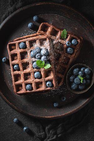 Tasty waffles made of chocolate on dark table
