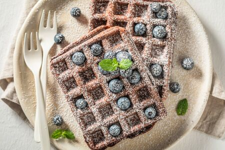 Top view of waffles with dark chocolate on white table