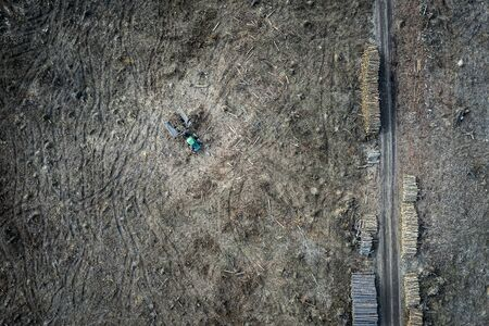 Flying above deforestation and small tractor, destroyed forest in Poland