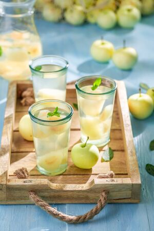 Tasty and fresh apple juice on blue wooden table Reklamní fotografie - 130115915