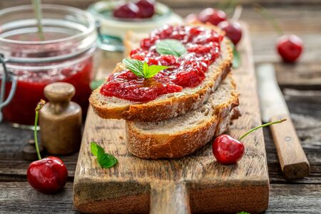 Tasty sandwich with jam made of cherries in garden Reklamní fotografie - 130116001