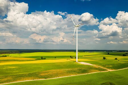 Big wind turbine on field in the summer, aerial view