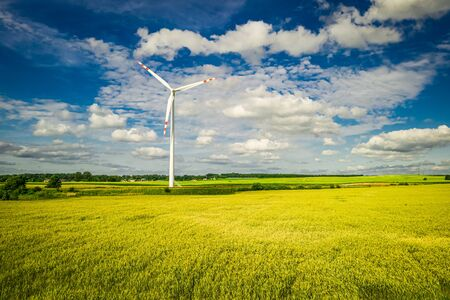 Flying above white wind turbine on field in the summer