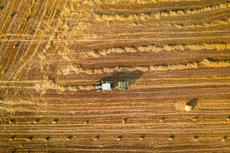 Tractor with round baler on fields, aerial view