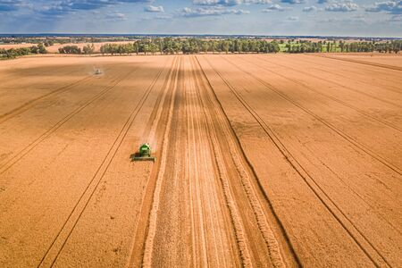 Flying above big field and small combine in Poland