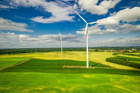 Flying above big wind turbine on field in the summer Banco de Imagens